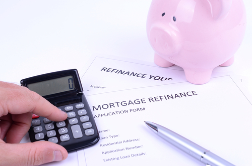 Person calculating mortgage options with a pink piggy bank