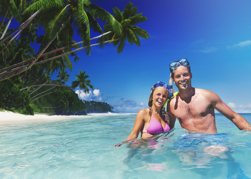 Couple snorkeling in blue water from getting perks from their credit card