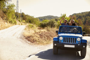 People riding in a blue jeep